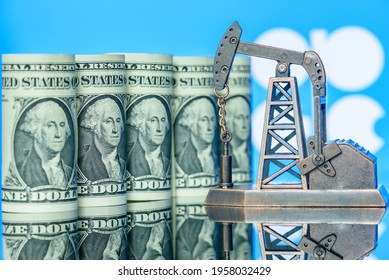 Petroleum, petrodollar and crude oil concept : US USD dollar banknotes, a pumpjack over flag of OPEC, depicts the money received or earned from sales after investment in the production of oil industry