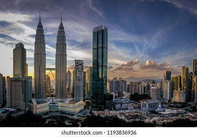 The Petronas Towers sit as the centerpiece of the skyline above the KLCC center on a blue, gold, and pink sunset night in the background
