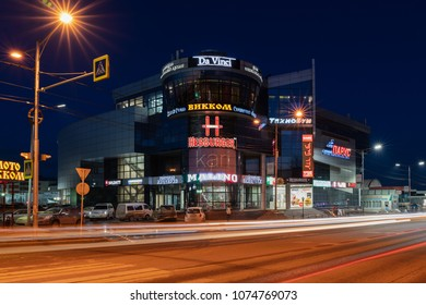 PETROPAVLOVSK CITY, KAMCHATKA PENINSULA, RUSSIA - 19 APRIL, 2018: Night view of building of shopping and entertainment center Sail and blurred traces of car headlights driving on central city road.