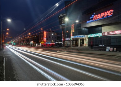 PETROPAVLOVSK CITY, KAMCHATKA PENINSULA, RUSSIA - 19 APRIL, 2018: Night view of blurred traces of automobile headlights driving on central city road and building of shopping, entertainment center Sail