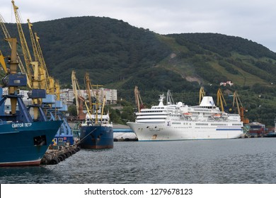 PETROPAVLOVSK CITY, KAMCHATKA PENINSULA, RUSSIA - 4 SEP, 2018: Summer view of Commercial Seaport of Petropavlovsk-Kamchatsky City on shore of Pacific Ocean - fishing ship and cruise liner at pier.