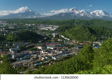PETROPAVLOVSK CITY, KAMCHATKA PENINSULA, RUSSIAN FAR EAST - JULY 8, 2018: Summer top view of Petropavlovsk-Kamchatsky City on background of majestic volcanoes surrounded by mountains with green forest