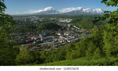 PETROPAVLOVSK CITY, KAMCHATKA PENINSULA, RUSSIAN FAR EAST - JULY 8, 2018: Summer panoramic cityscape of Petropavlovsk-Kamchatsky on background of majestic volcanoes surrounded by mountains.