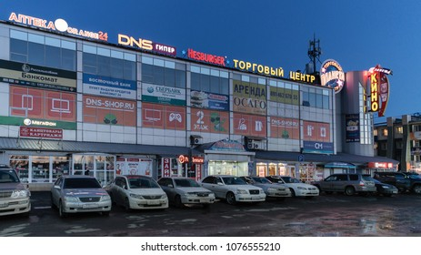 PETROPAVLOVSK KAMCHATSKY CITY, KAMCHATKA PENINSULA, RUSSIAN FAR EAST - 19 APRIL, 2018: Night view of facade building of shopping center Planet and cars parked in parking lot in front of store.
