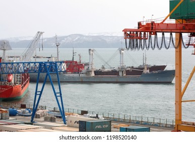 PETROPAVLOVSK KAMCHATSKY, KAMCHATKA PENINSULA, RUSSIA - NAY 20, 2018: Ships at pier, port cranes on commercial seaport Petropavlovsk-Kamchatsky City on shore of Avacha Bay in Pacific Ocean.