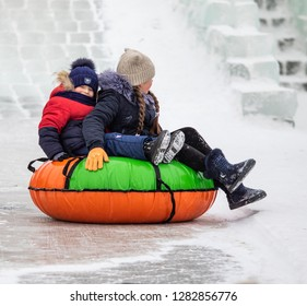 PETROPAVLOVSK, KAZAKHSTAN - JANUARY 13, 2019: Children ride on an icy hill. Adults and children relax in the park together.