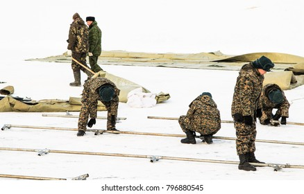 Petropavlovsk, Kazakhstan - January 18, 2018: Soldiers put up a tent in the snow. Preparation for Epiphany bathing hole. Christian tradition.