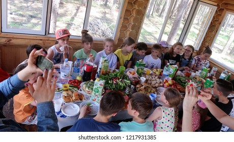 Petropavlovsk, Kazakhstan - June 3, 2017: Children and parents sit at the table eating, forest nature park.
