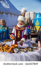 PETROPAVLOVSK, KAZAKHSTAN - MARCH 21, 2015: celebration of the new year on the solar calendar astronomical in Iranian and Turkic peoples. Kazakh girl pours mare