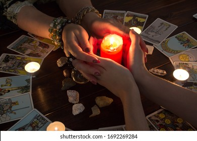 Petropavlovsk, Kazakhstan, March.15.20.Female hands hold a lighted candle in the dark at night. A fortune teller performs a magical. Ritual of enchantment and clairvoyance. Seance and prediction