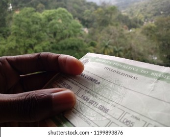 "PETROPOLIS, RIO DE JANEIRO - BRAZIL - OCT, 7 2018: Brazilian voter prepared to vote displays voter's title, required by country's legislation (translation: ""Federative Republic of Brazil, voter title)"