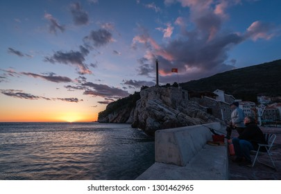 Petrovac, Montenegro - April 2018 : Fisherman catching fish with fishing rods in Petrovac bay on the Adriatic sea