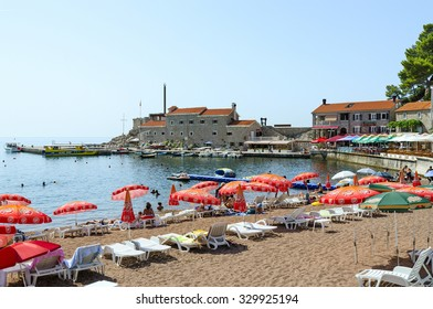 PETROVAC, MONTENEGRO - SEPTEMBER 19, 2015: Unidentified people are relaxing on the beach of waterfront near the old Venetian fortress in the popular resort town of Petrovac, Montenegro