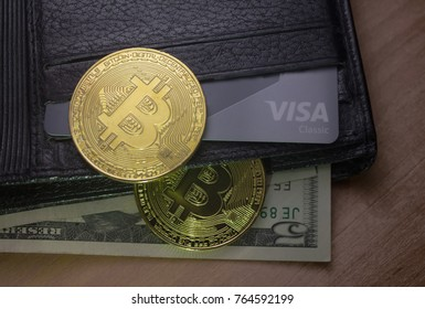 Petrozavodsk. Karelia. Russia. November 26. 2017: Two coins of bitcoin on a black wallet with dollars and a visa card