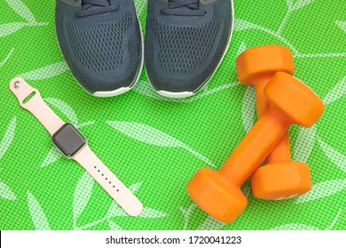 Petrozavodsk, Russia - 29 april, 2020: Sports equipment - orange dumbbells, sneakers and a fitness watch to control your health
