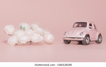 Petrozavodsk, Russia - April 04, 2019: Pink toy retro car on pink background, next to white roses, holidays concept