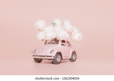 Petrozavodsk, Russia - April 04, 2019: Pink retro toy car with bouquet of white Roses on pink background. Concept Valentine's day, February 14 card, 8 March, International Happy Women's Day