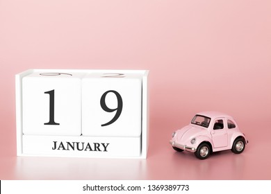 Petrozavodsk, Russia - April 06, 2019: Close-up wooden cube 19th of January. Day 19 of january month, calendar on a pink background with retro car. Winter time. Empty space for text.