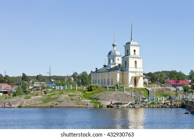 PETROZAVODSK, RUSSIA - MAY 29TH, 2016: Christian orthodox church on the shore of Lake Onega on a rock, the locals catching fish near the church in Petrozavodsk, Republic of Karelia, Northern Russia