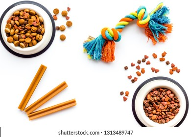 Pets accessories in home. Dog food in bowl and toys on white background top view