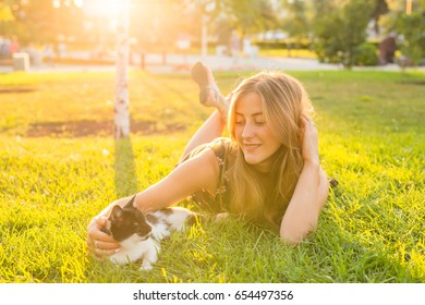 Pets and owner concept - Beautiful girl playing with a cat in the grass.