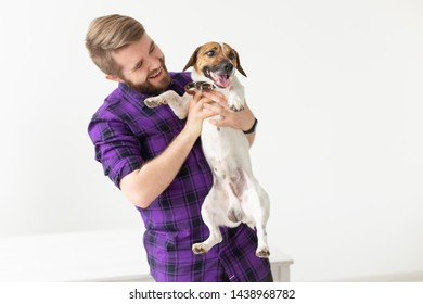 Pet's owner concept - young man playing with puppie on white background