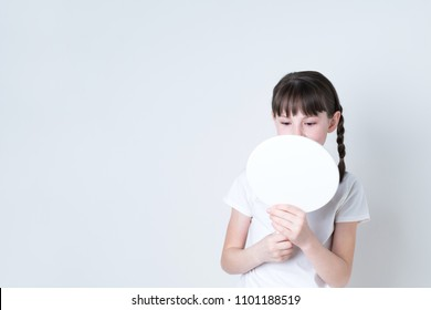 Petty girl checking her favial skin with a hand mirror.