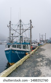 Petty Harbour, Newfoundland, Canada - June 21, 2019: Fishing vessel Theresa & Lisa sits docked in Petty Harbour on a foggy first day of summer. Vertical, portrait.