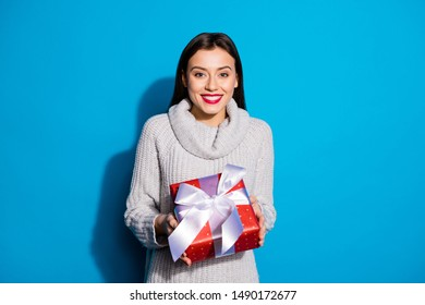 Petty lady taking big red giftbox wear knitted pullover isolated blue background
