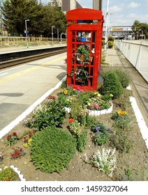 Petunias in hanging baskets on display, in garden made from old red London telephone box, on railway station platform.