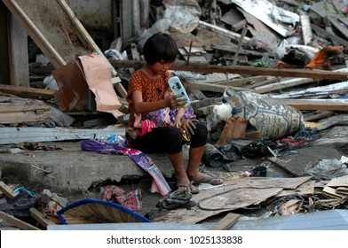 Peunayong Banda Aceh, Aceh, Indonesia - January 7, 2005: A Girl taking care of her sister while waiting for their mother. their homes destroyed when Earthquake & Tsunami in December 26 2004