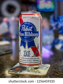 Pewaukee, Wisconsin/USA-November 27, 2018:  12 ounce can of Pabst Blue Ribbon beer on a bar counter with a coaster.