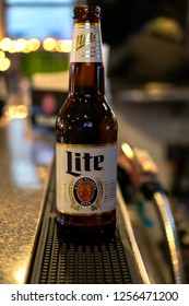 Pewaukee, Wisconsin/USA-November 27, 2018:  Brown beer bottle of Miller Lite shot from side looking down a bar.  Blurry background.