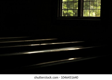 pews in darkness and reflection from glass