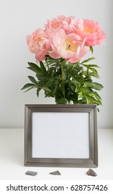 Pewter finish metal photo frame mock-up with bouquet of peonies