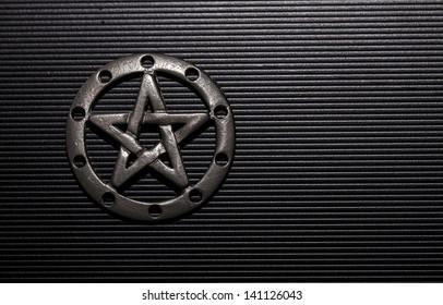 Pewter pentacle on black background