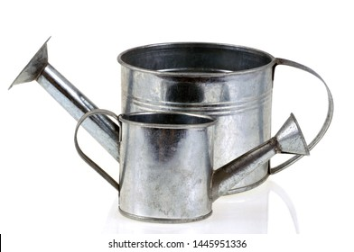 Pewter watering can of different sizes close up on white background