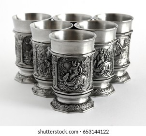 Pewter wine goblets with relief The Song of the Nibelungs isolated on a white background with shallow depth of field