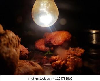 Peyaji pakoda onion fry dal pakoda Golgappa chaat potato fry chop alu chop jhuri papdi fuchka in glass box kept crisp and warm dry by light bulb heat