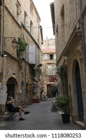 PEZENAS, FRANCE-JULY 21, 2016: Man sitting on a bench on a street in the city of Pezenas, Herault in southern of France