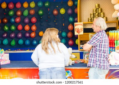 Pfalz / Germany: October 6 2018: market. An obese child is standing in front of a fun fair stall with her father. Concept of obesity in childhood and enjoying life.