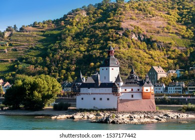 Pfalzgrafenstein Castle, known as the Pfalz, a famous toll castle on the Falkenau island, on the Rhine river. Beautiful vineyards in autumn morning light.