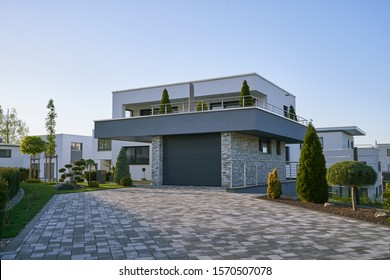 Pforzheim, Germany - April 21, 2019: New modern cube-shaped house with a garage in front of a facade in a new area against a blue sky. Modern house without a fence