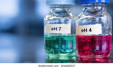 pH 7 (green) and 4 buffer (red) solutions in glass bottles. These calibration solutions are commonly found in science laboratories where meters are used to measure sample acidity or alkalinity.