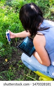 PH meter tester in soil. Measure soil with digital device and tablet. Woman farmer in a garden. Concept for new technology in the agriculture.