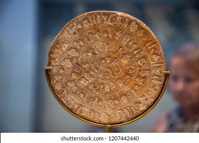 Phaistos Disk, an undecoded clay disk  from Minoan palace of Phaistos, Crete dating to Minoan Bronze Age. It is exhibited in the Archaeological Museum in Crete island. Heraklion, Greece - May 31, 2018