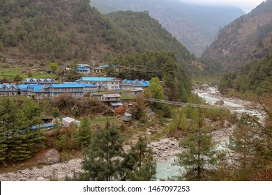 Phakding village stands on the riverbank of Dudh Koshi snow river (Dudh Kosi river or Milk-Koshi River) in Nepal. Suspension bridge connects two riverbanks. Nature, Countryside and Travel concept.