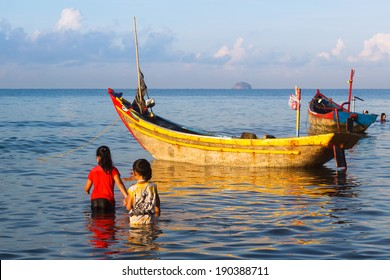 PHAN THIET, VIETNAM - MAY 01: An unidentified boy and girl playing beside fishing boat at morning, Mui Ne, Phan Thiet, Vietnam. On May 01, 2013.