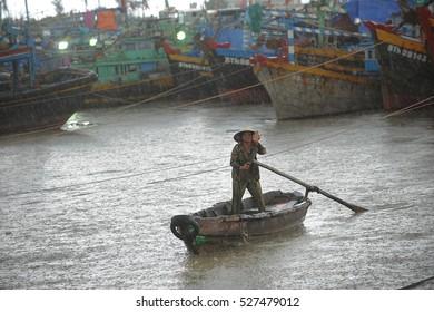 Phan Thiet, Vietnam, september 05, 2012:  Vietnamese fishermen moor to the quay in the rain Phan Thiet, Vietnam
