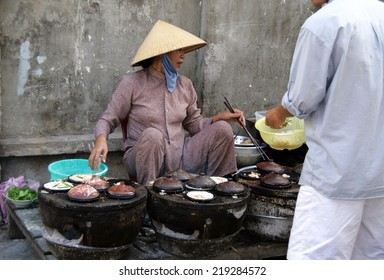 PHAN TIET, VIET NAM - FEB 10, 2009: Vietnamese woman on the street market selling snacks, heated on a special oven on coals